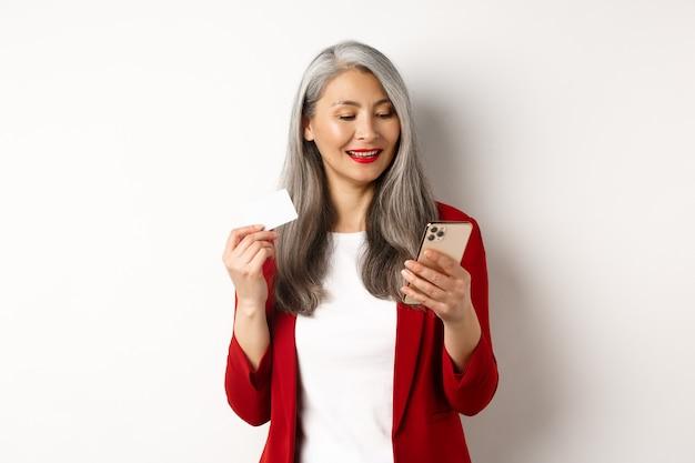 Femme senior asiatique en tenue élégante effectuant le paiement en ligne, tenant une carte de crédit en plastique et un smartphone, fond blanc.