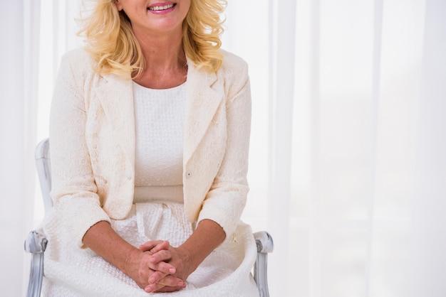 Femme senior blonde souriante assise sur une chaise blanche