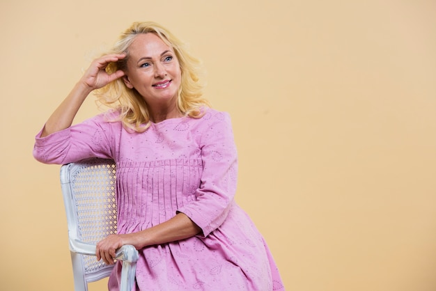 Femme senior blonde vêtue d'une robe rose avec espace de copie
