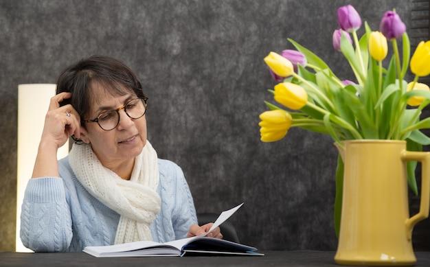 Femme senior brune avec des lunettes de lecture livre