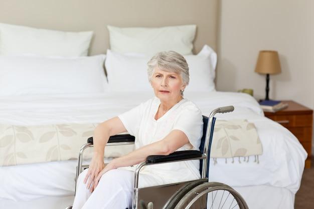 Femme senior concentrée dans son fauteuil roulant à la maison