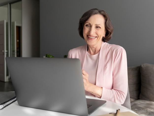 Femme senior de coup moyen avec ordinateur portable