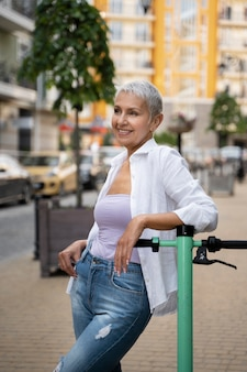 Femme senior de coup moyen avec scooter