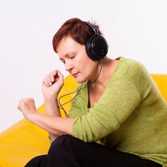 Femme senior détendue écoutant de la musique