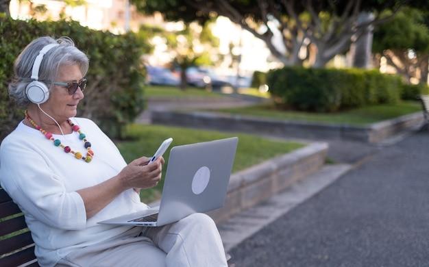 Femme senior élégante assise sur un banc de parc à l'aide d'un téléphone portable et d'un ordinateur portable. elle porte des écouteurs pour la vidéoconférence et travaille à l'extérieur