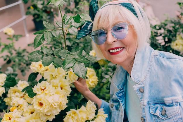 Femme senior élégante en veste en jean faisant du selfie avec des fleurs jardinage voyageant ambiance positive