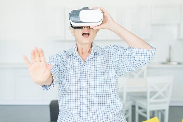 Femme senior étonnée touchant l'air pendant l'expérience de réalité virtuelle
