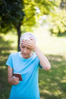 Femme senior inquiète lit un message sur un téléphone mobile
