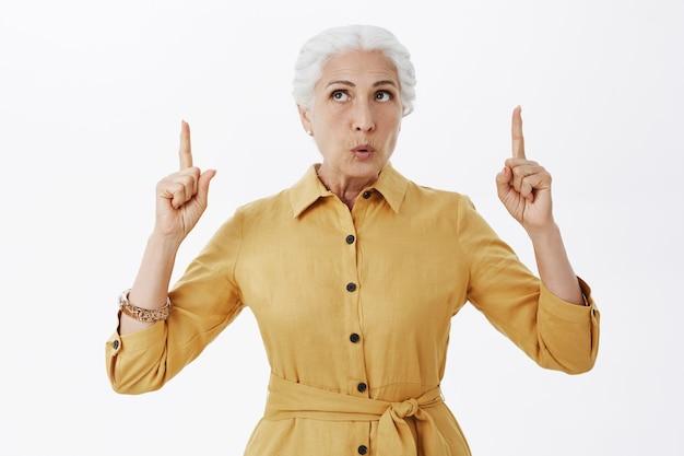 Femme senior intriguée et curieuse à la recherche et pointant les doigts vers le haut