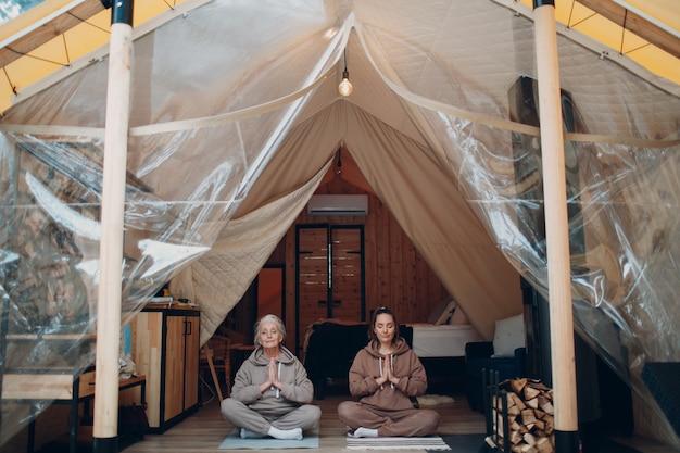 Femme senior et jeune détente à la tente de camping glamping. famille de femmes grand-mère âgée et jeune petite-fille faisant du yoga et de la méditation à l'intérieur. concept de style de vie de vacances moderne et zen.