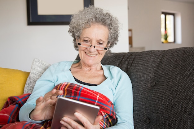 Femme senior joyeuse lire un livre intéressant à l'aide d'une tablette