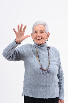 Femme senior avec une main ouverte et numéro cinq sur fond blanc