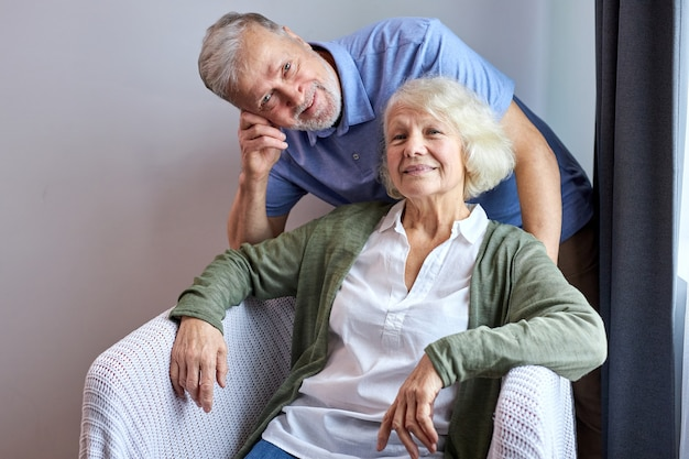 Femme senior et mari posant souriant sur un canapé confortable à la maison, femme assise tandis que son mari se tient derrière elle. portrait