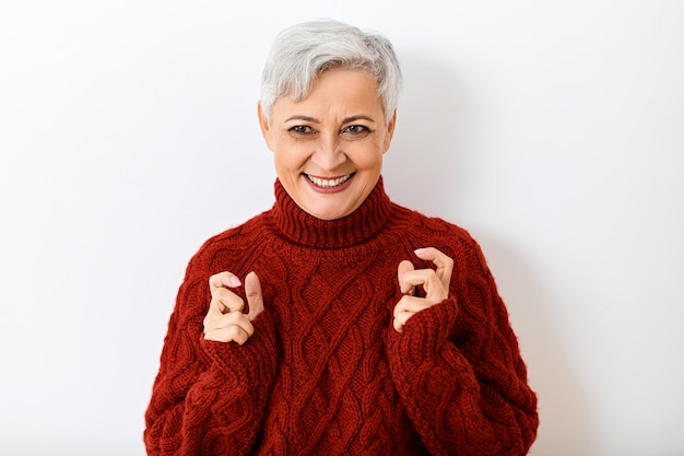 Femme senior mature aux cheveux gris en pull tricoté élégant exprimant l'excitation et la joie, regardant avec un large sourire rayonnant, se tenant la main comme si serrant quelque chose. réactions et sentiments humains