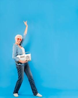 Femme senior moderne avec radio vintage