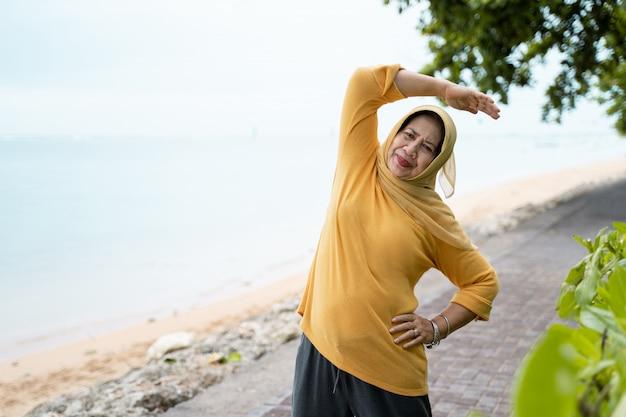 Femme senior musulmane qui s'étend et exerce à l'extérieur