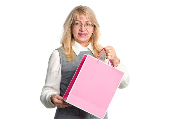 Femme senior avec un paquet rose sur fond blanc.