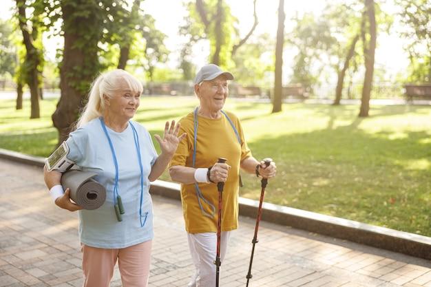 Femme senior positive avec tapis et homme avec des bâtons pour la marche nordique dans un parc verdoyant