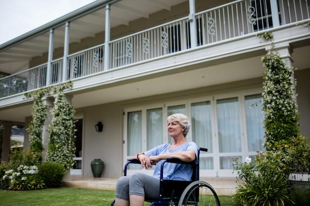 Femme senior réfléchie assise sur un fauteuil roulant