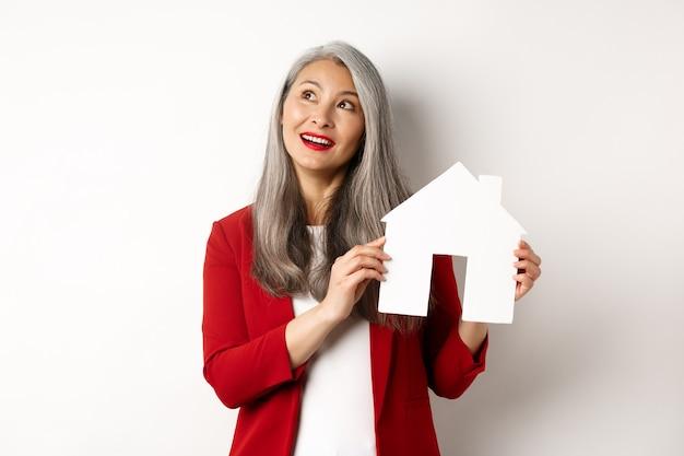 Femme senior rêveuse pense à acheter une propriété, montrant la découpe de maison en papier et en regardant le coin supérieur gauche, debout sur fond blanc.