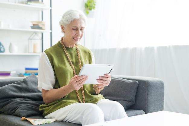 Femme senior souriante assise sur un canapé en regardant une tablette numérique