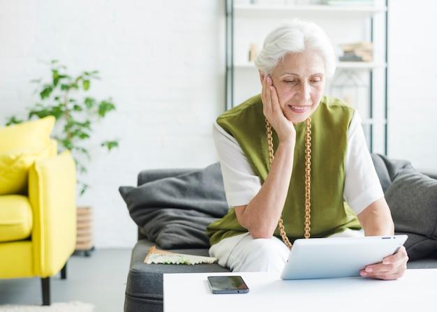 Femme senior souriante assise dans le salon en regardant une tablette numérique