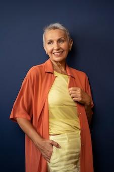 Femme senior souriante de coup moyen posant