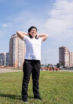 Femme senior souriante, échauffement avant de s'entraîner à l'extérieur dans le parc sur scène urbaine