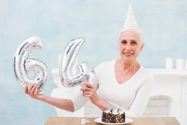 Femme senior souriante montrant un ballon en feuille de 64 numéros avec son gâteau d'anniversaire sur la table