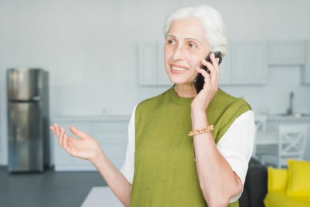 Femme senior souriante parlant sur les gestes mobiles