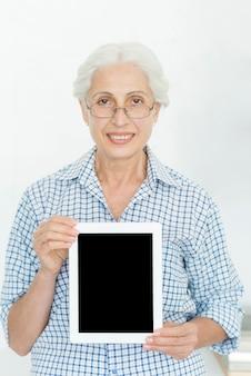Femme senior souriante portant des lunettes montrant une tablette numérique avec écran blanc