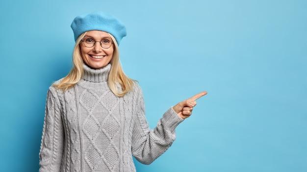 Femme senior souriante positive pointe l'index sur l'espace de copie vierge sur le mur bleu