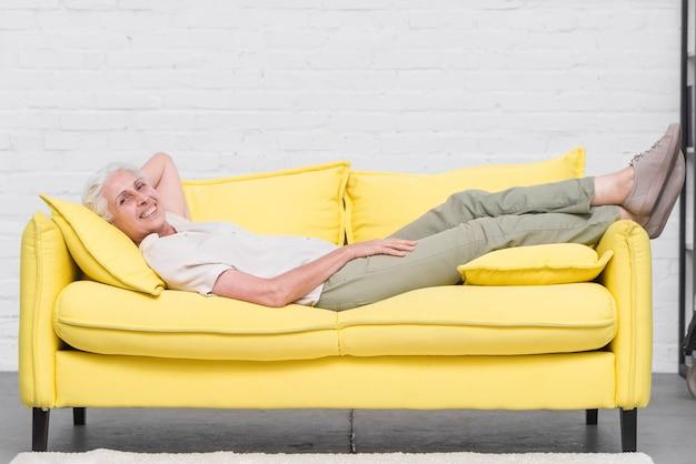 Femme senior souriante reposante sur un canapé jaune à la maison