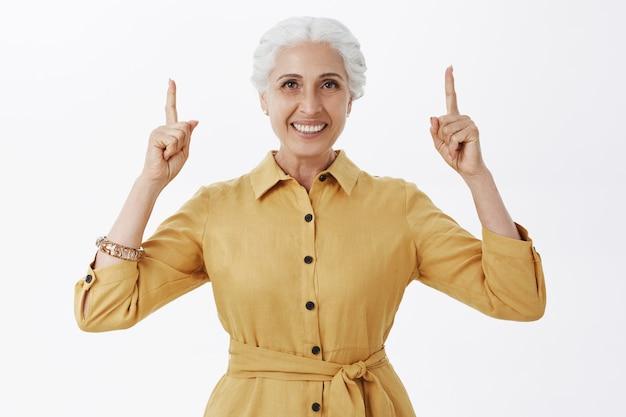 Femme senior souriante en trench jaune pointant les doigts vers le haut