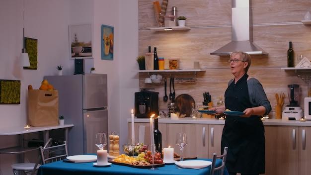 Femme senior surprenant son mari avec un dîner romantique. vieux couple de personnes âgées parlant, assis à table dans la cuisine, savourant le repas, célébrant leur anniversaire avec des aliments sains.