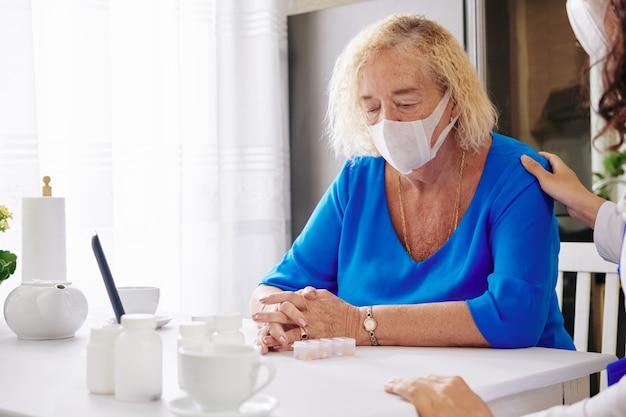 Femme senior triste dans un masque médical