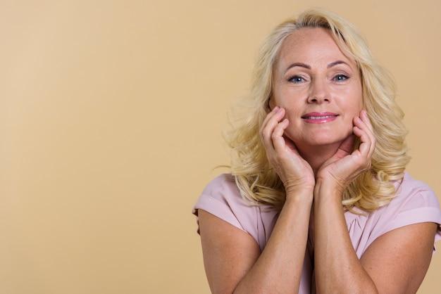 Femme senior vue de face en regardant la caméra avec un fond beige