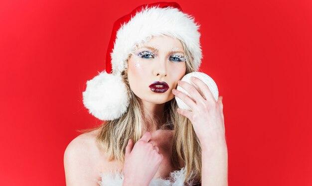 Femme sensuelle en bonnet de noel avec boule de sapin de noël. temps de noël et célébration du nouvel an. vacances d'hiver.