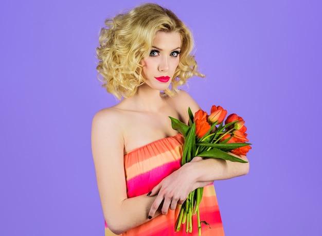 Femme sensuelle avec bouquet de tulipes, belle fille aux fleurs de printemps.