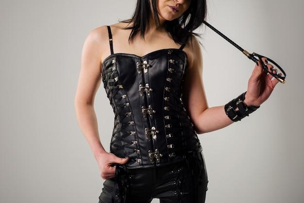 Femme sensuelle en corset de cuir noir avec cravache à la main