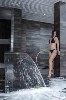 Femme sensuelle debout près de la cascade dans la piscine spa