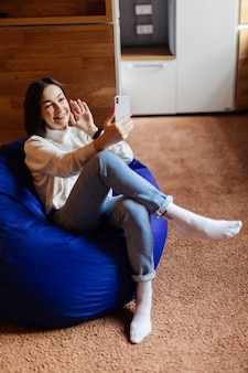 Femme sensuelle en jean bleu et t-short blanc faire selfie avoir un appel vidéo sur son téléphone