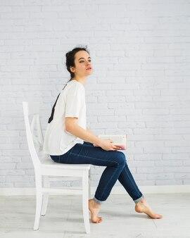 Femme sensuelle avec un livre sur une chaise