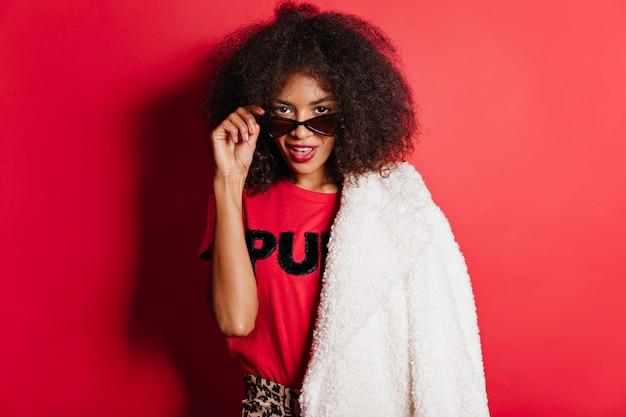 Femme sensuelle en manteau et lunettes de soleil debout sur un mur rouge