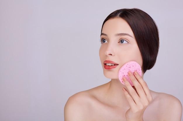 Une femme sensuelle nettoie son visage