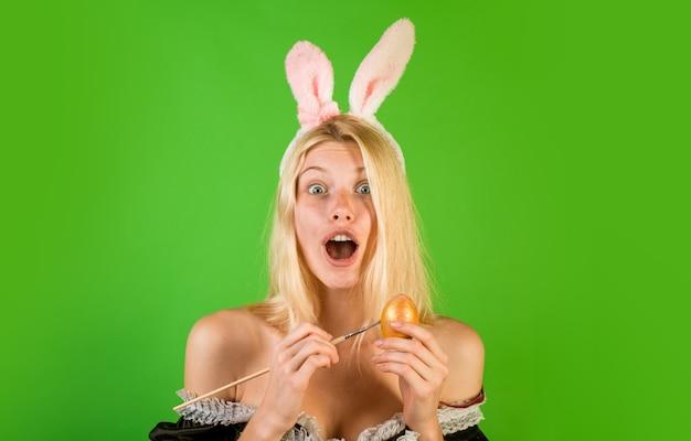 Femme sensuelle portant des oreilles de lapin et tenant des oeufs de pâques colorés a l'air surpris à la caméra.