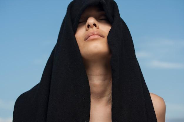 Femme sensuelle avec une serviette noire sur la tête