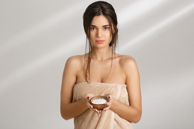 Femme sensuelle tenant un gommage au sel dans les mains, regardant droit.