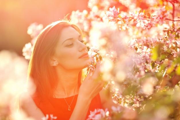 Femme sent les fleurs dans le jardin de printemps