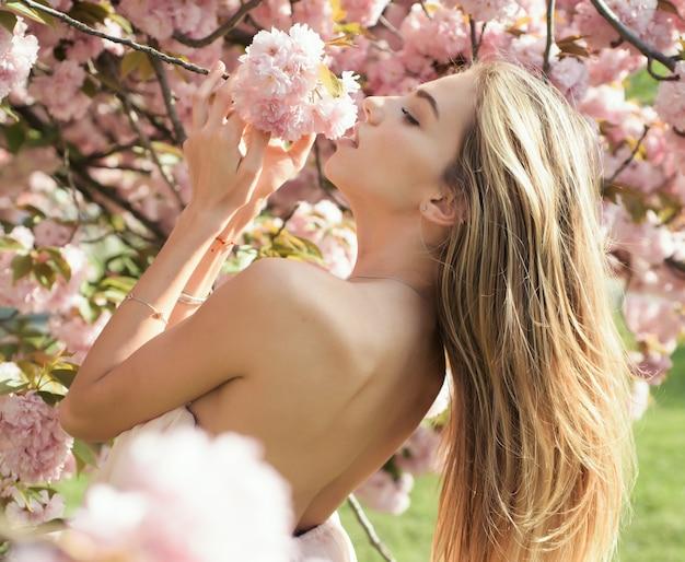 Femme sentant l'arôme frais de cerises japonaises fille de printemps en robe rose courte profitant d'une journée ensoleillée dans le jardin femme sexy posant sous l'arbre de fleurs de cerisier en fleurs